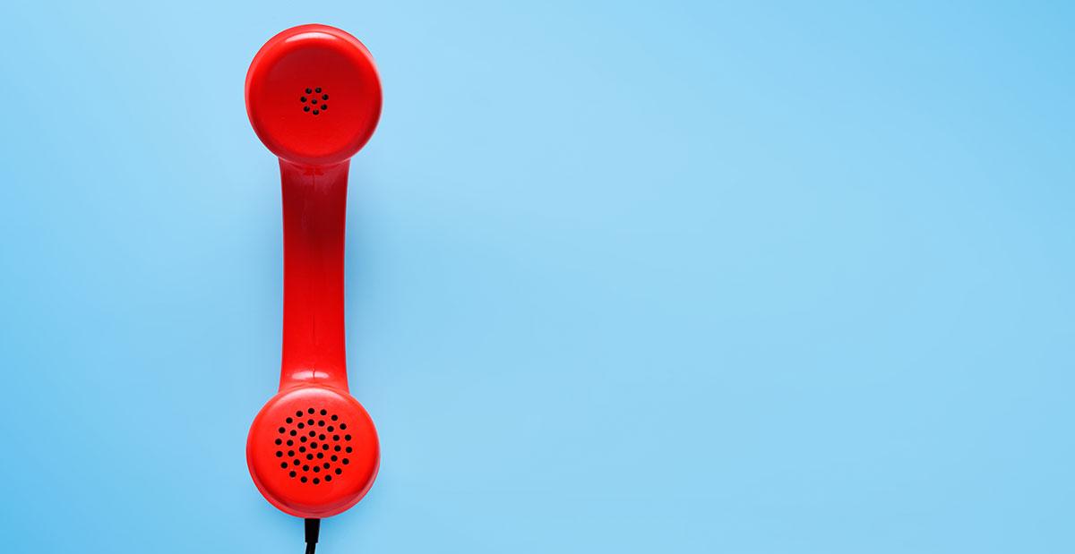 Ein alter roter Telefonhörer auf blauem Grund