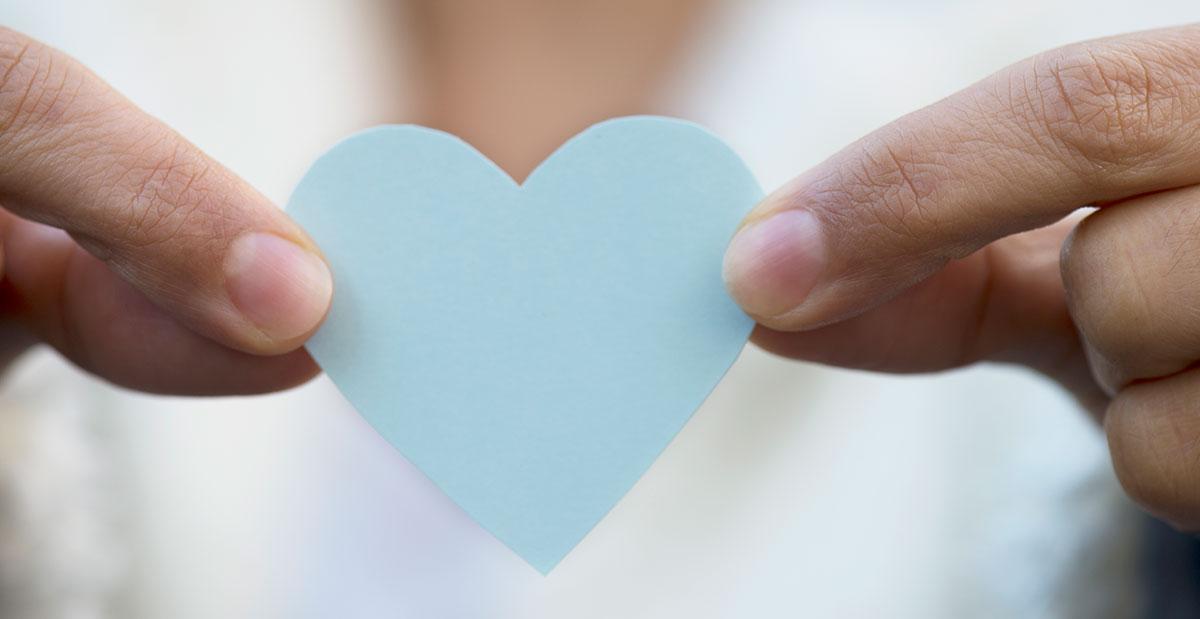 Zwei Hände halten ein hellblaues Herz aus Papier
