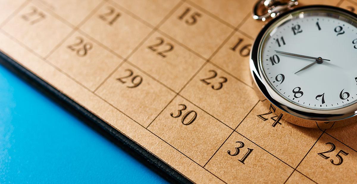 Ein Kalender und eine Taschenuhr auf blauem Grund